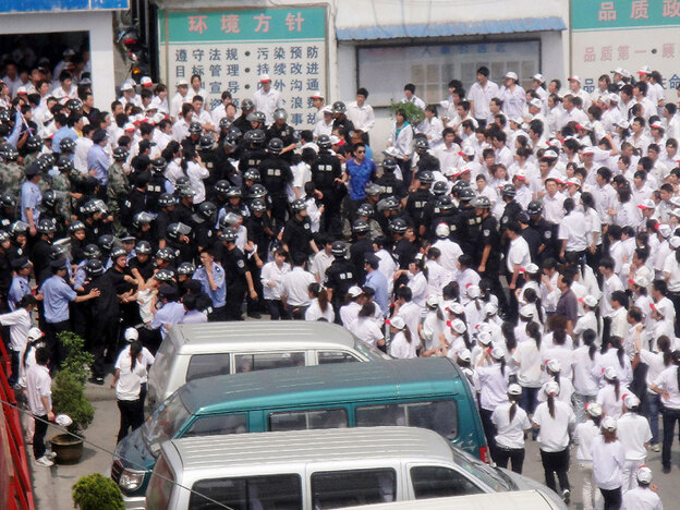 Some 2,000 Chinese workers clash with police as they stage a strike outside the  Taiwan-funded KOK Machinery rubber factory in Kunshan, east China's Jiangsu province, on June 7.