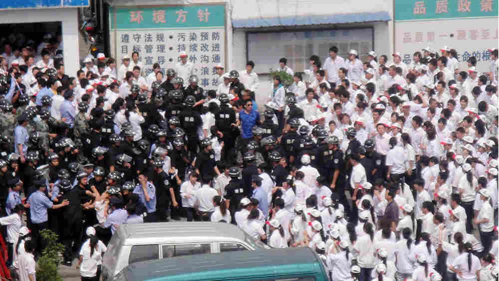 Workers clash with police at KOK Machinery rubber factory in Kunshan, Jiangsu.