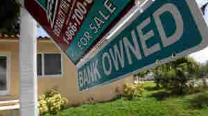 A 'bank owned' sign is posted in front  of a foreclosed home in Miami.