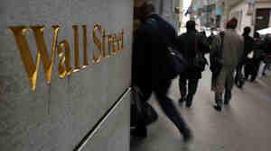 People walk down Wall Street