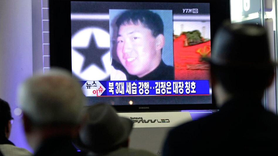 South Koreans  at the Seoul Railway  Station watch Tuesday as a TV news program shows a portrait of Kim Jong Un. The youngest son of  North  Korea's leader Kim Jong Il is being  groomed as the country's next leader, but little is known about him.