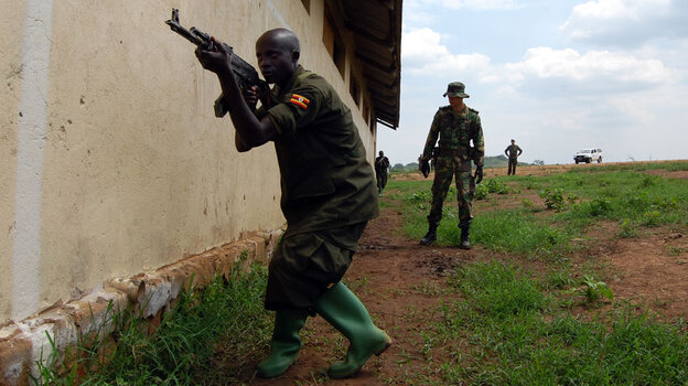 A European soldier oversees training of a Somali soldier at a training camp in Uganda