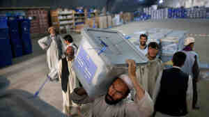 Workers shift ballot boxes at the Independent Election Commission warehouses on Sept. 23.