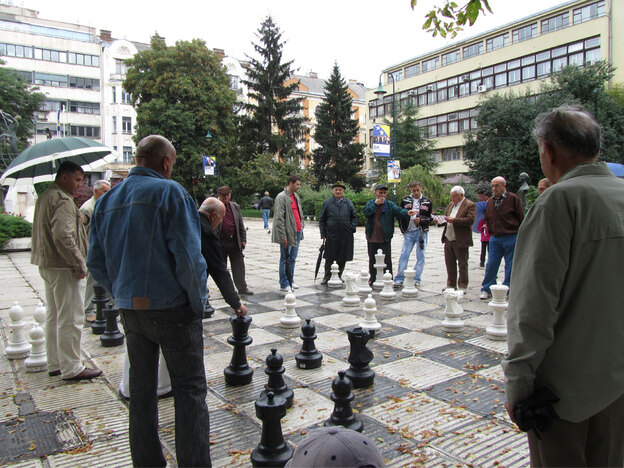 Fifteen years after the war, the routine of life goes on in Bosnia-Herzegovina. Here, men in a Sarajevo park play chess on a giant board.