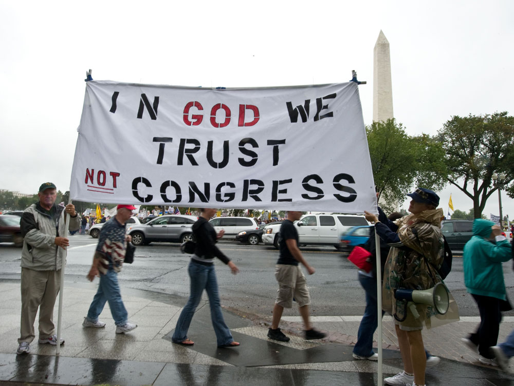 Tea Party supporters hold a sign in front of the Washington Monument during a march on Sept. 12.