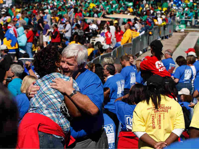 Erica DeVose, left, is hugged by Mike Crossey
