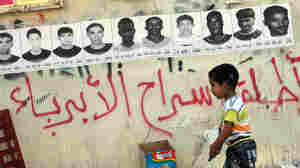 A boy walks past posters of political detainees in Bahrain.