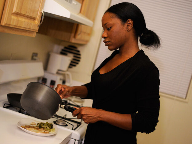 Jada Irwin prepares dinner in the kitchen of her apartment.