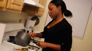 Jada Irwin prepares dinner in the kitchen of her apartment.