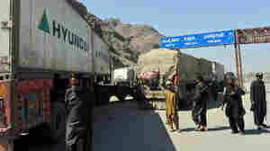 Pakistani security personnel stand beside trucks carrying NATO supplies at Torkham, Pakistan.