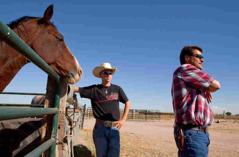 Terry Walter (right) and his son Ty stand next to one of the horses they use to round up cattle.