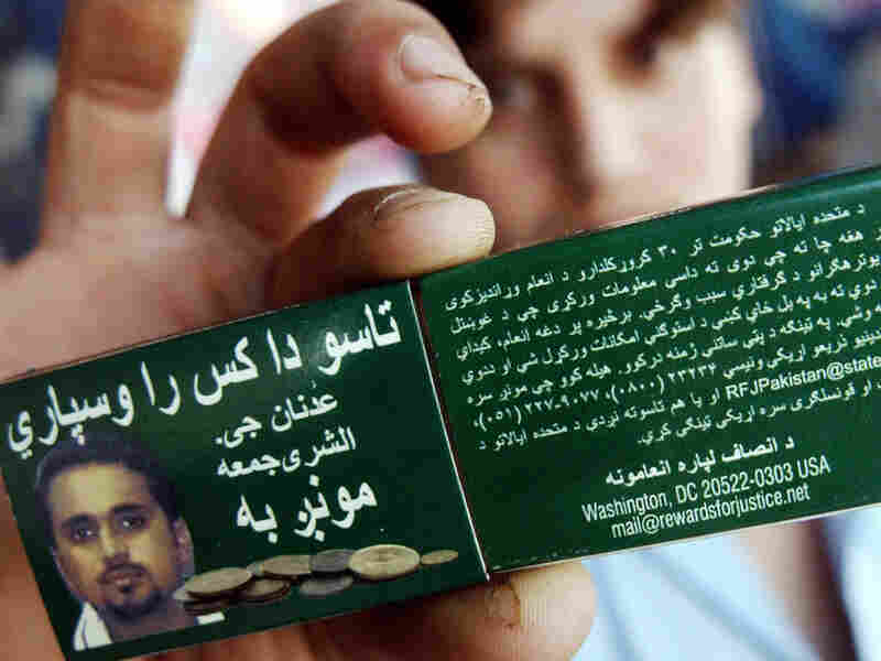 A Pakistani man in Peshawar holds a matchbox with a photo of Shukrijumah