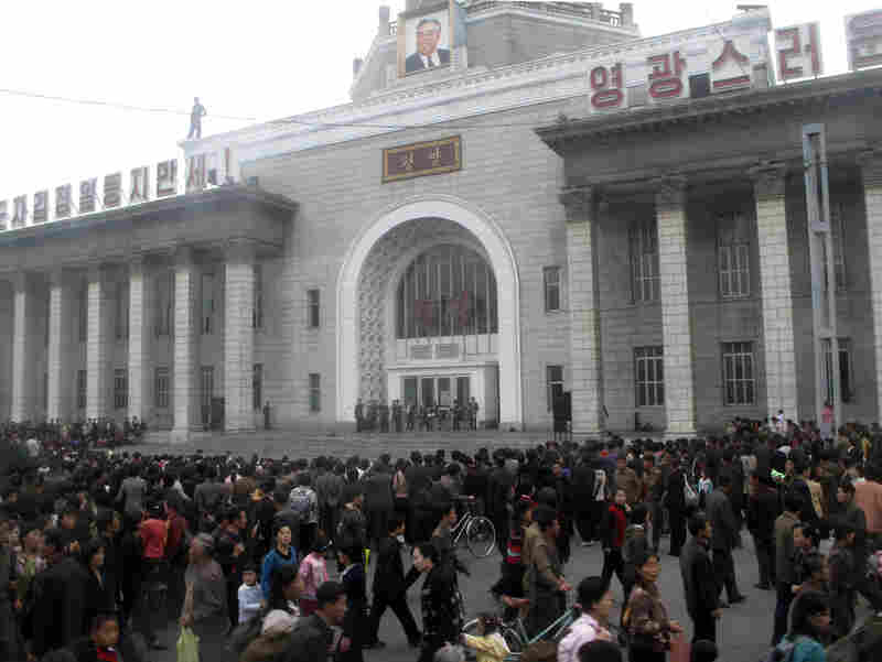 North Koreans attend a rally at a train station.