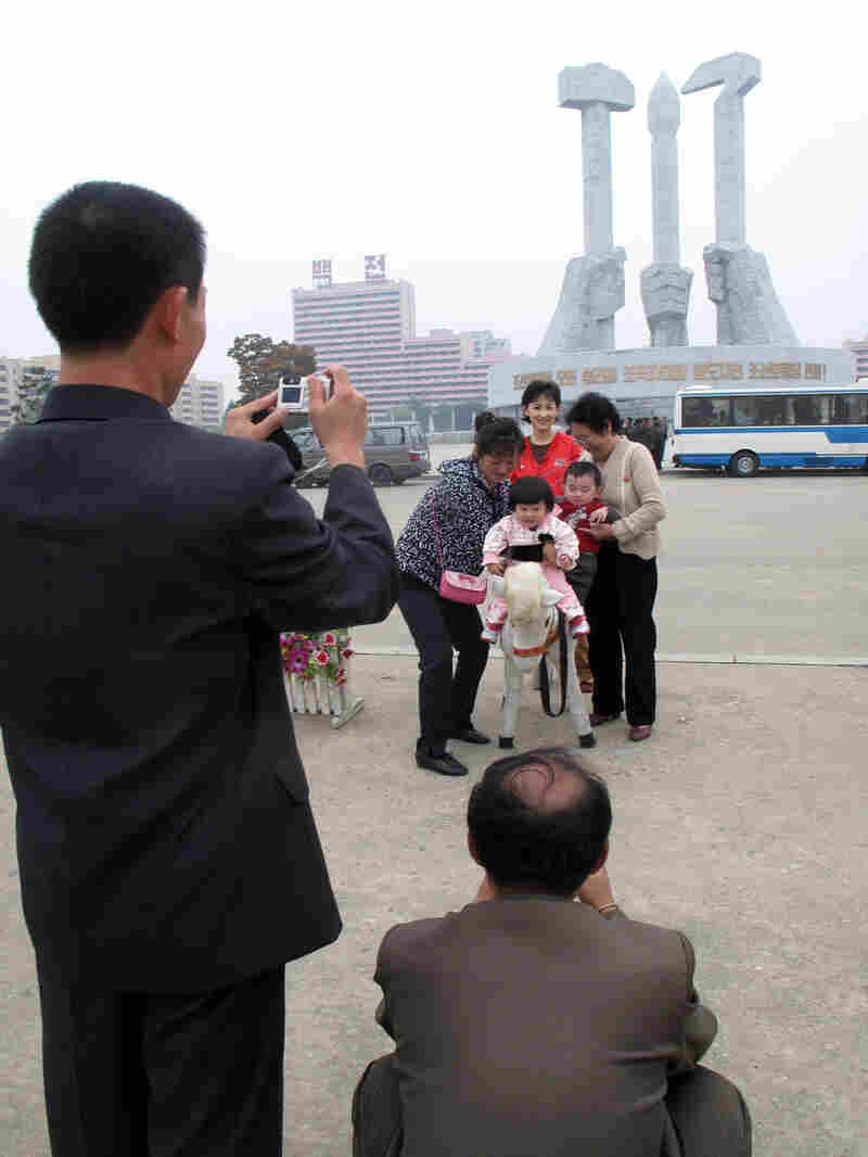 Family poses for photos in front of the monument to the foundation of the Workers Party in Pyongyang