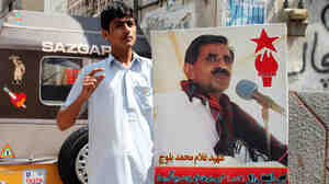 In Karachi's Baluch Para neighborhood, a Baluch man holds up poster of a nationalist leader