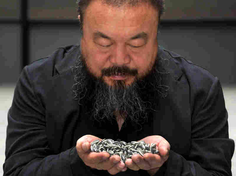 Artist Ai Weiwei holds porcelain sunflower seeds from his installation