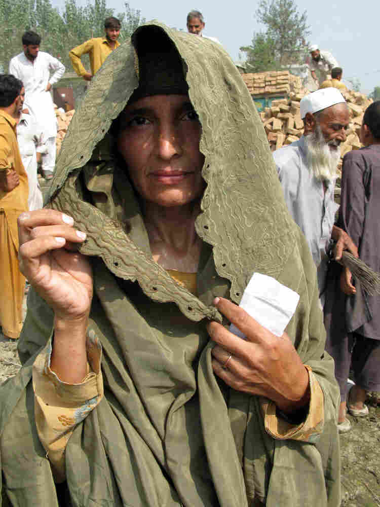 Wajahat Bibi, a mother of six, lifts her veil to have her photo taken.