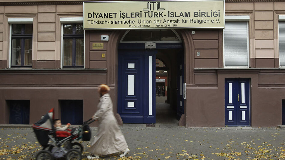 A Muslim woman wearing a headscarf walks past a Turkish religious organization in Berlin's Kreuzberg district. Many Germans still refer to those of Turkish descent — even if they're third-generation German citizens — as <em>Die Turken,</em> the Turks. Many see this as proof that along with education and immigration reform, a change in mentality will be necessary to deal with multicultural society.