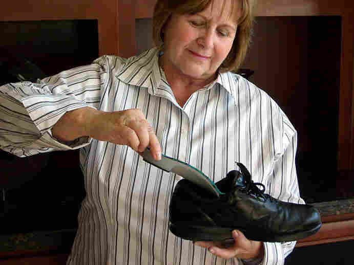 Robin Bentz puts an orthotic into a shoe