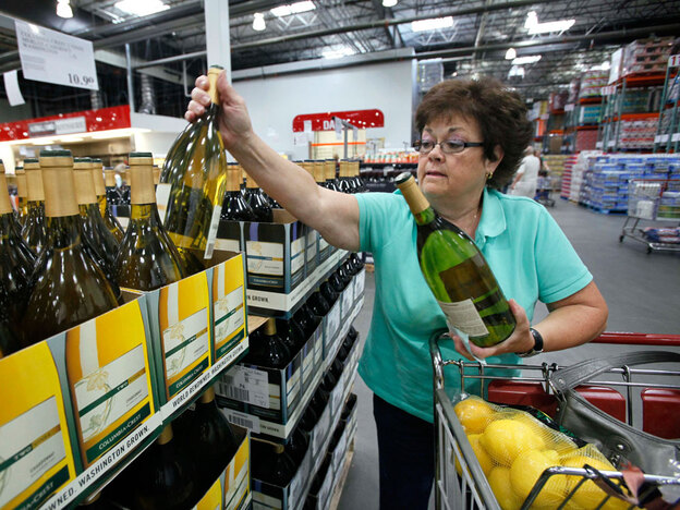 Georgia LaBelle reaches for a bottle of wine as she shops at a Costco warehouse store in Seattle. Costco is putting financial muscle behind a Washington ballot initiative to do away with state-run liquor stores.