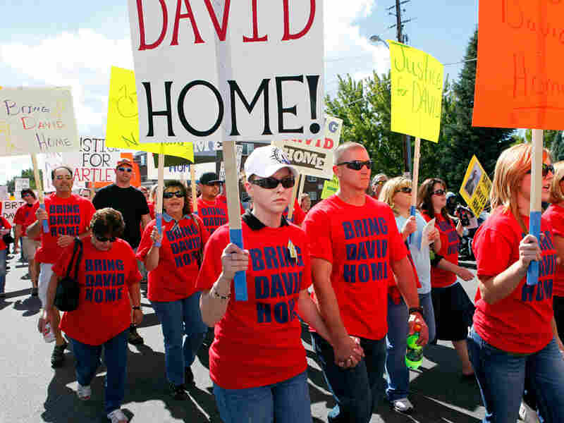 Friends and supporters of David Hartley march in an effort to have his body returned to the United States.