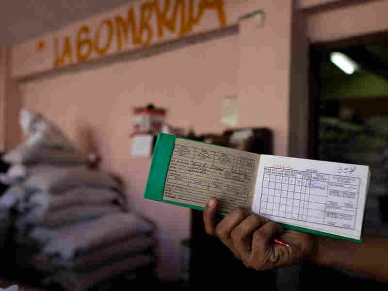 A customer displays his ration card as he waits to buy food at a government store in Havana in October 2009