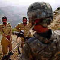 Army Lt. Kenneth Kovach speaks to Pakistani border police over wire that separates Afghanistan and Pakistan