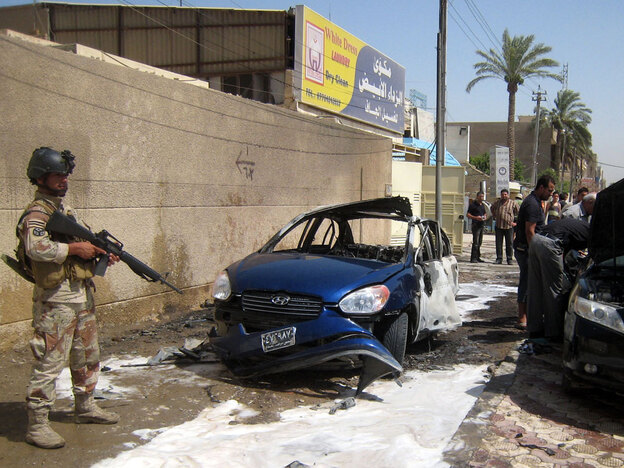 An Iraqi  soldier stands guard after the detonation of a sticky bomb plastered to a  vehicle belonging to an employee of the Iraqi Parliament in the Mansur district  of Baghdad in June. The explosion injured two people.
