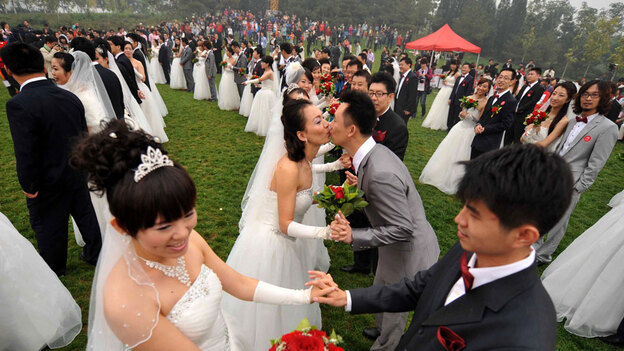 Despite China's advances over the past few decades, when it comes to marriage, tradition holds sway. Here, 200 newlywed couples pose at the National Stadium in Beijing, Oct. 10, 2010. (AFP/Getty Images)