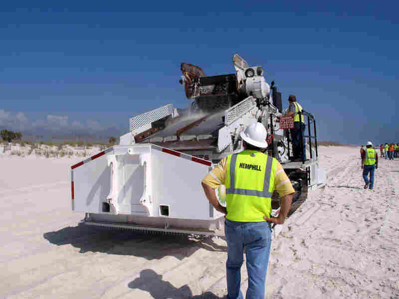 "An earth-moving machine dubbed ""Ozzie"" digs up oily sand and sifts out the tar balls."