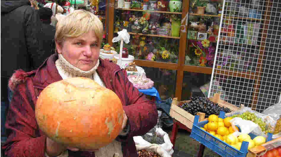 Vegetable seller Olesya Vladymyrovna holds a pumpkin