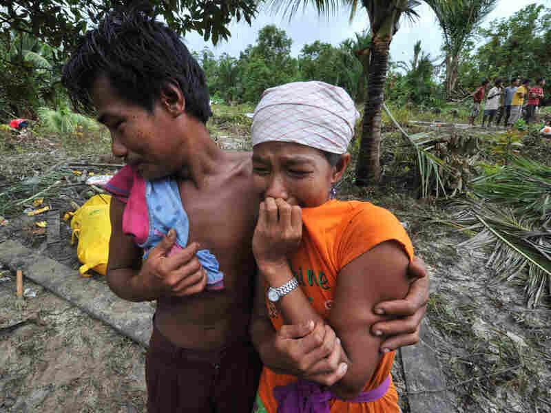 Survivors mourn their dead relatives