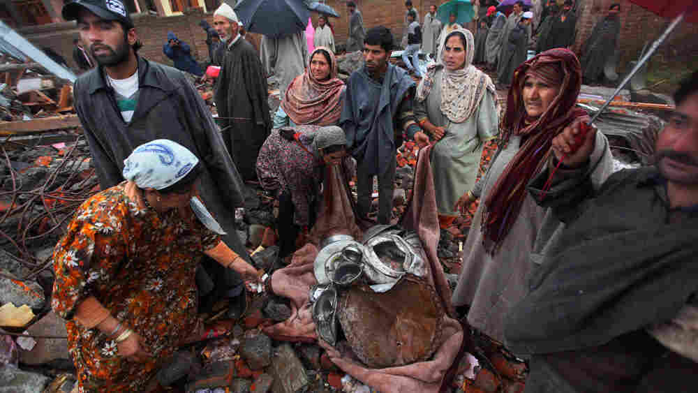 Kashmiris salvage their belongings after a gun battle between separatists and Indian troops