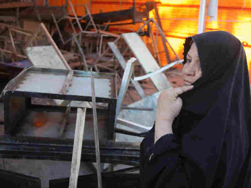 An Iraqi woman stands next to a cafe destroyed by a car bomb in Baghdad