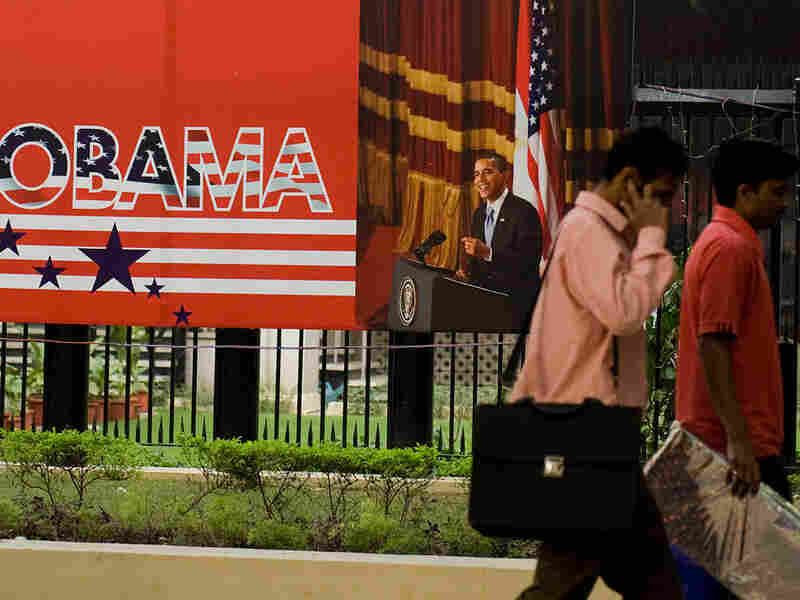 Indian pedestrians walk past a billboard welcoming President Obama in New Delhi