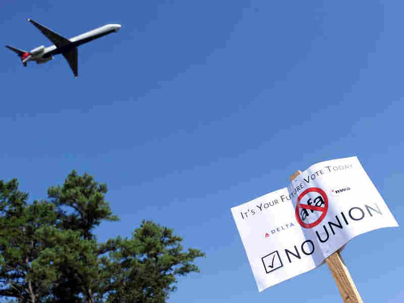 A Delta Air Lines employee holds an anti-union sign during a rally.