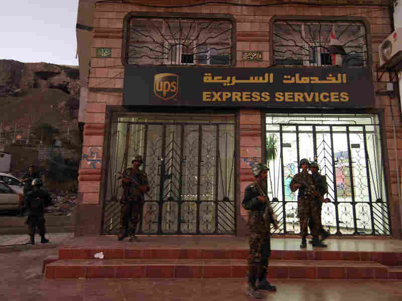 Yemeni security guards outside a branch of the U.S. package delivery firm UPS in Yemen