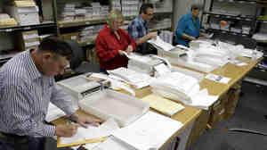Election workers count ballots yesterday in Juneau.