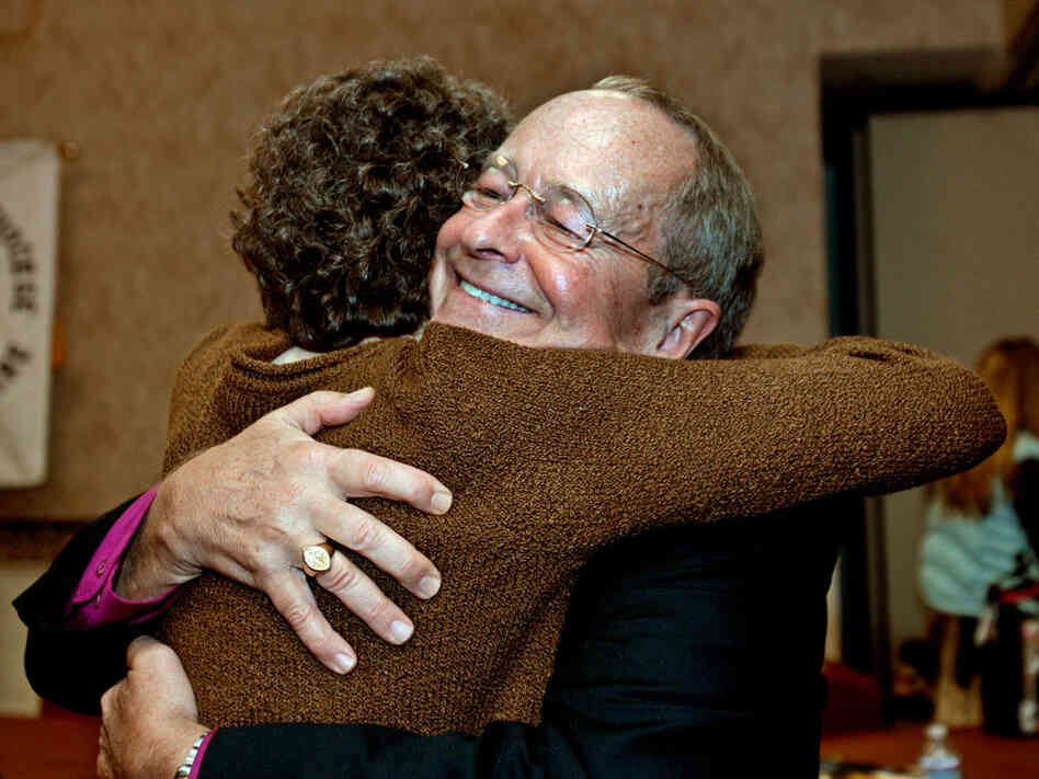 Bishop V. Gene Robinson, right, hugs a friend after announcing his retirement on Saturday.