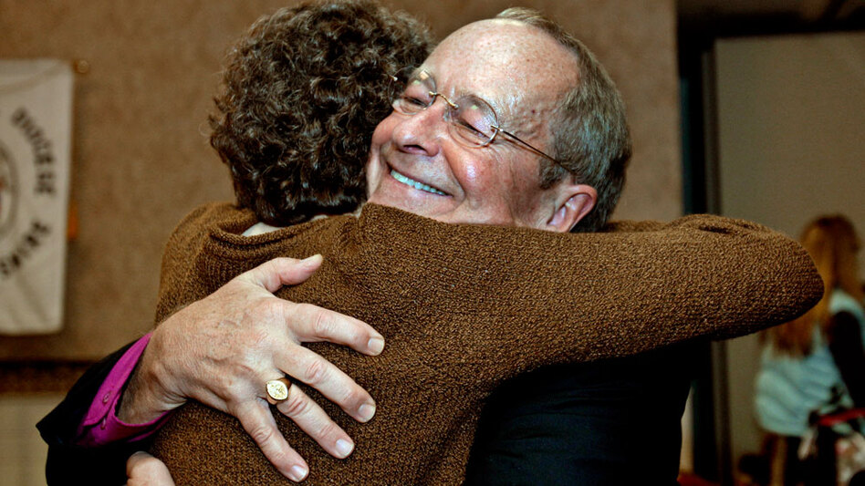 New Hampshire Bishop V. Gene Robinson, the first openly gay Episcopal bishop in the global Anglican fellowship, hugs Margaret Porter after announcing his retirement at the annual diocesan convention in Concord, N.H., Nov. 6, 2010.