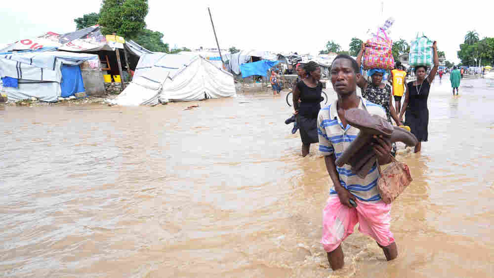 Haitians walk along a flooded road south of Port-au-Prince