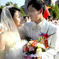Chinese newlyweds pose during a collective wedding ceremony in Shanghai