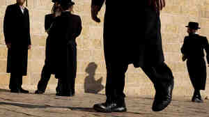 Ultra-Orthodox Jewish men walk at the Western Wall in Jerusalem.