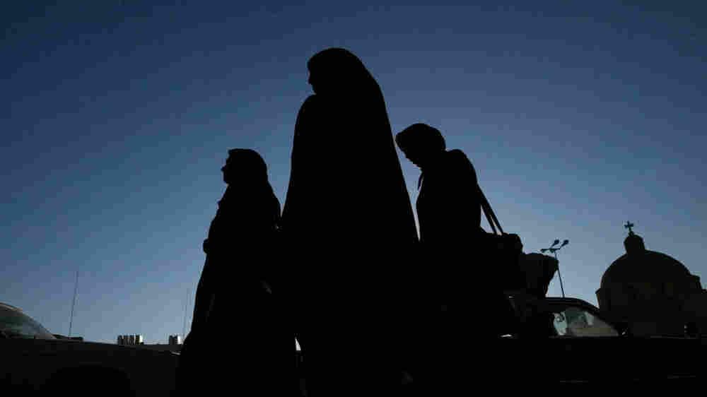 Iraqi women walk along a street in Baghdad.