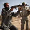 An Afghan policeman receives weapons training from U.S. soldiers outside Kandahar City