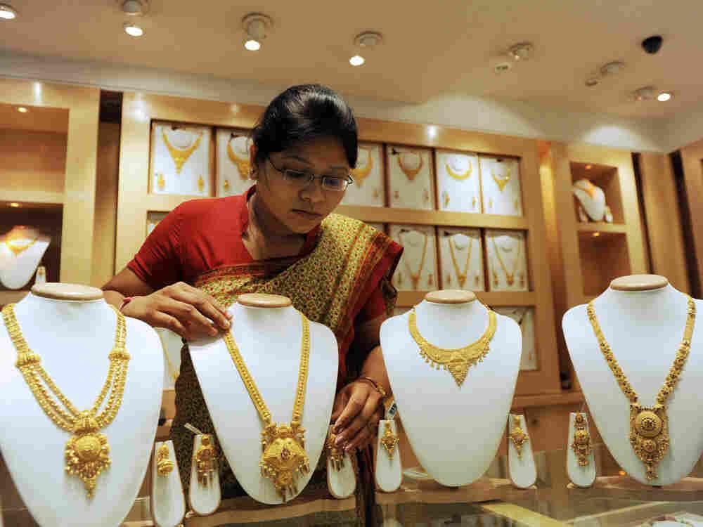 A saleswoman arranges 22-carat gold necklaces.