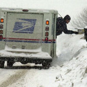 A letter carrier delivers mail in a snowstorm.