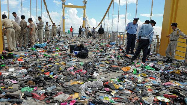 Police examine belongings on a bridge in Phnom Penh