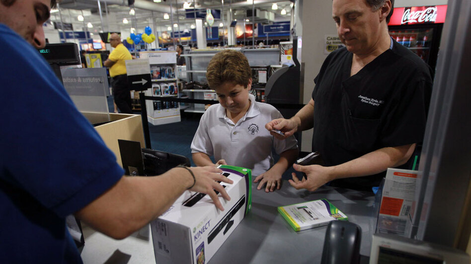 Peter Martin sells Microsoft's new Kinect controller for the Xbox 360 to Jonathan Hyde and his son Lucas at a Best Buy store in Miami Beach.