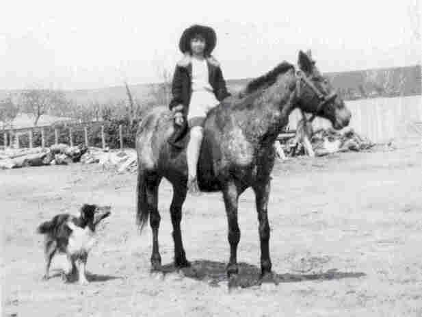 Ellene riding her horse Midget while her dog Trigger walks along beside them.